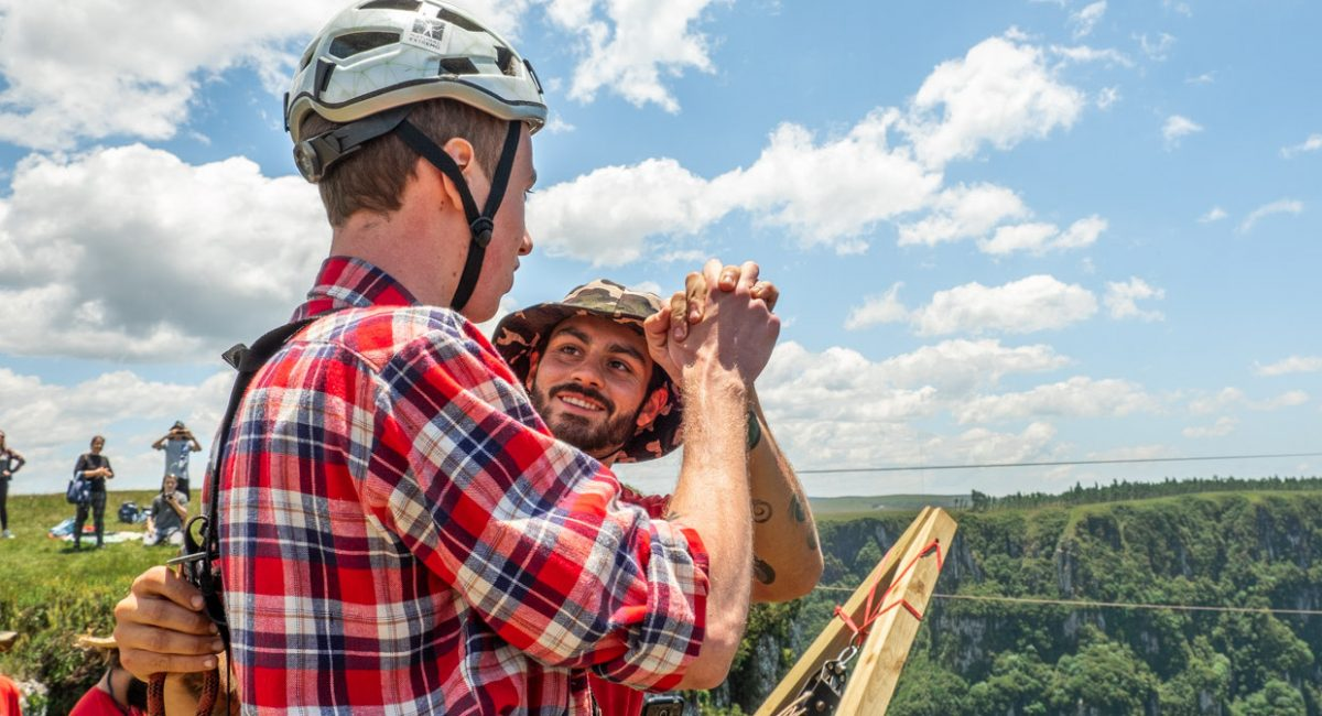 Foto de pessoas tocando as mãos em um High Five no salto de pêndulo